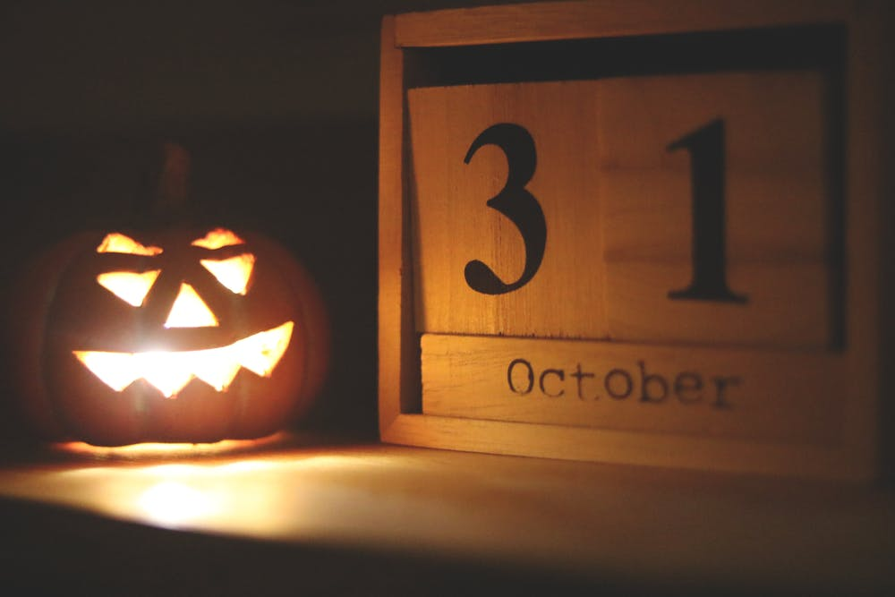 A jack-o-lantern sits to the left of wooden numbers 3 and 1